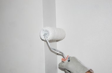 Hand painting a wall with a paint roller