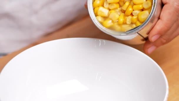 Ruce nalévání kukuřičných zrn v kovové plechovce do misky, kukuřice konzervované zboží non-zkáza potraviny skladování produkty v domácnosti kuchyně.
