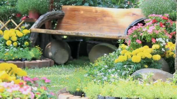 Wood swing in the flowers garden, HD vdo.