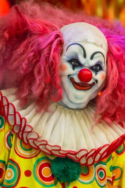 Scary clown doll smiling.