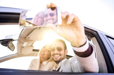 Young couple taking a selfie in car