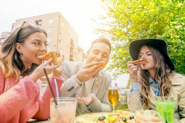 Cheerful people eating pizza and drinking beer outdoors