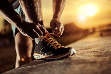 Man tying jogging shoes