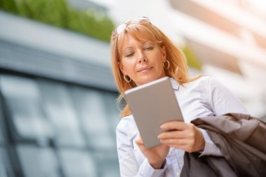 Mature businesswoman working on a digital tablet