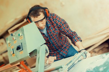 Carpenter with automatic circular saw. He has protective glasses