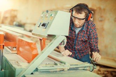 Carpenter using circular saw in his workshop