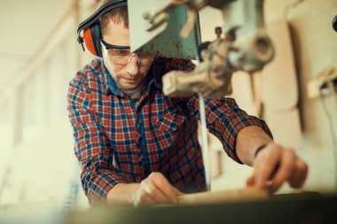 Close up of a young carpenter at work.He is using a bandsaw.