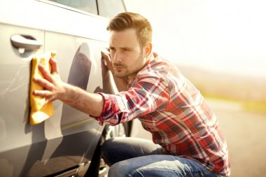 Man with a microfiber wipe the car polishing