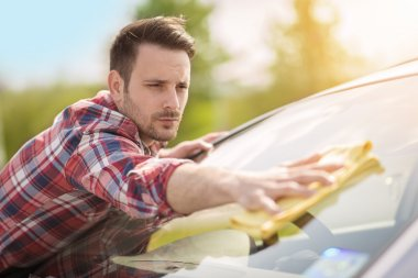 Young man cleaning his car outdoors