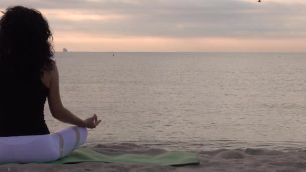 A nő lótuszpózban pihen a parton. Meditáció a tenger közelében napkeltekor.