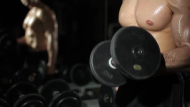 Chlap v tělocvičně. Dělá cvičení s činkami.
