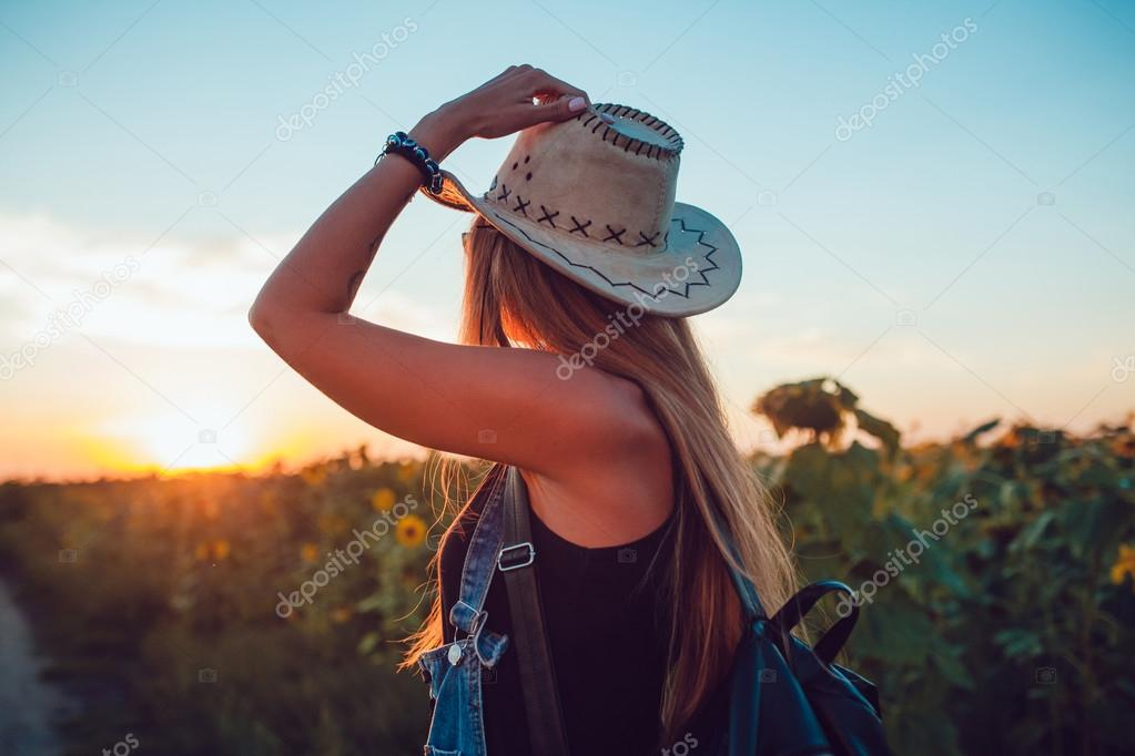Girl In A Cowboy Hat In A Sunflower Field Sunset Stock Photo