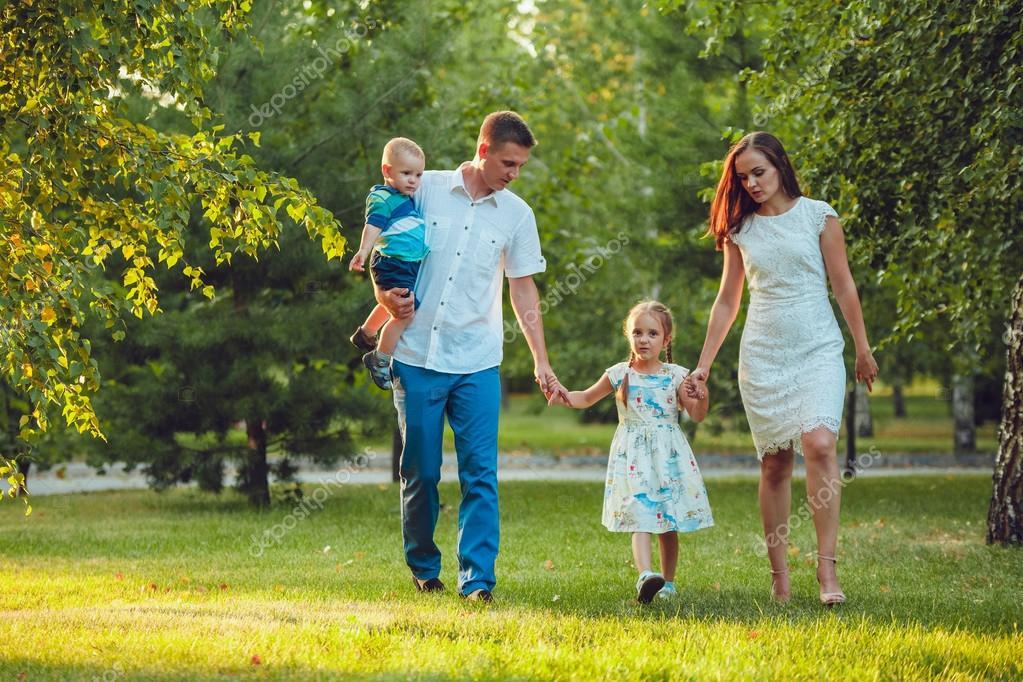 Familia Joven Feliz De Cuatro Personas Caminando Y La