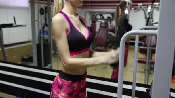 Beautiful sporty woman doing exercises on the simulator. Abdominal muscles. Bright leggings.