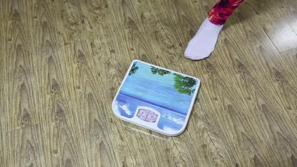 Dívka měří váhu na podlahové váhy. Detail ponožky