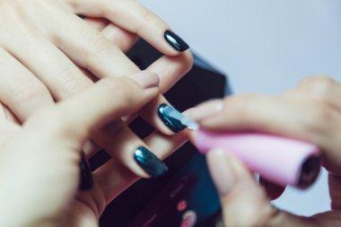 Manicure. Beauty saloon. Close-up. Apply black nail polish.