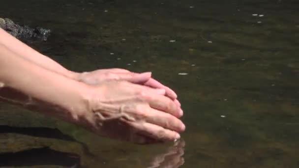 Közeli kép a kezek scooping tiszta víz, tiszta hegyi tavasszal