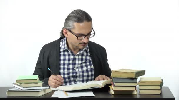muž sedící u stolu studiu a psaní v poznámkovém bloku
