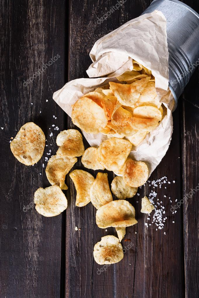 Potato chips over dark wooden background