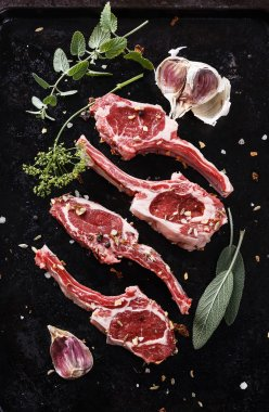 Lamb cutlets on a black textured metal tray