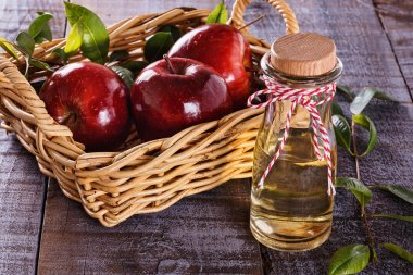 Apple cider vinegar over rustic wooden background