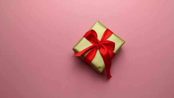 Festliches Geschenk in Goldverpackung und roter Schleife auf rosa Hintergrund. Ein angenehmes Geschenk und eine Überraschung für die Lieben.