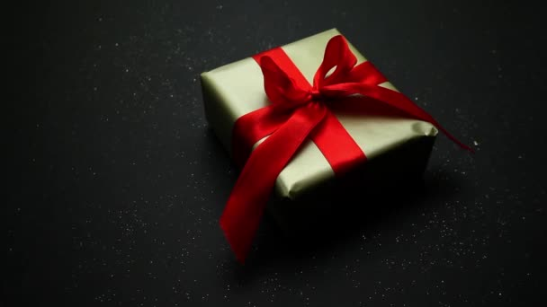 Ünnepi ajándék arany csomagolásban és piros masni fekete háttérrel. Kellemes ajándék és meglepetés szeretteinknek..