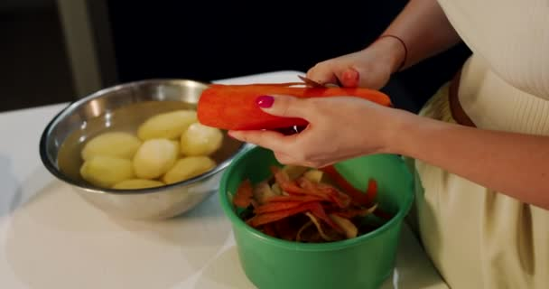 A girl, a young woman, prepares food and cleans vegetables, ingredients.