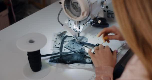 Žena, návrhářka oblečení, stříhá nůžky v dílně.