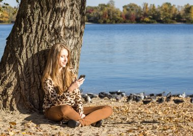 Young girl sitting on the beach and looking at mobile phone screen