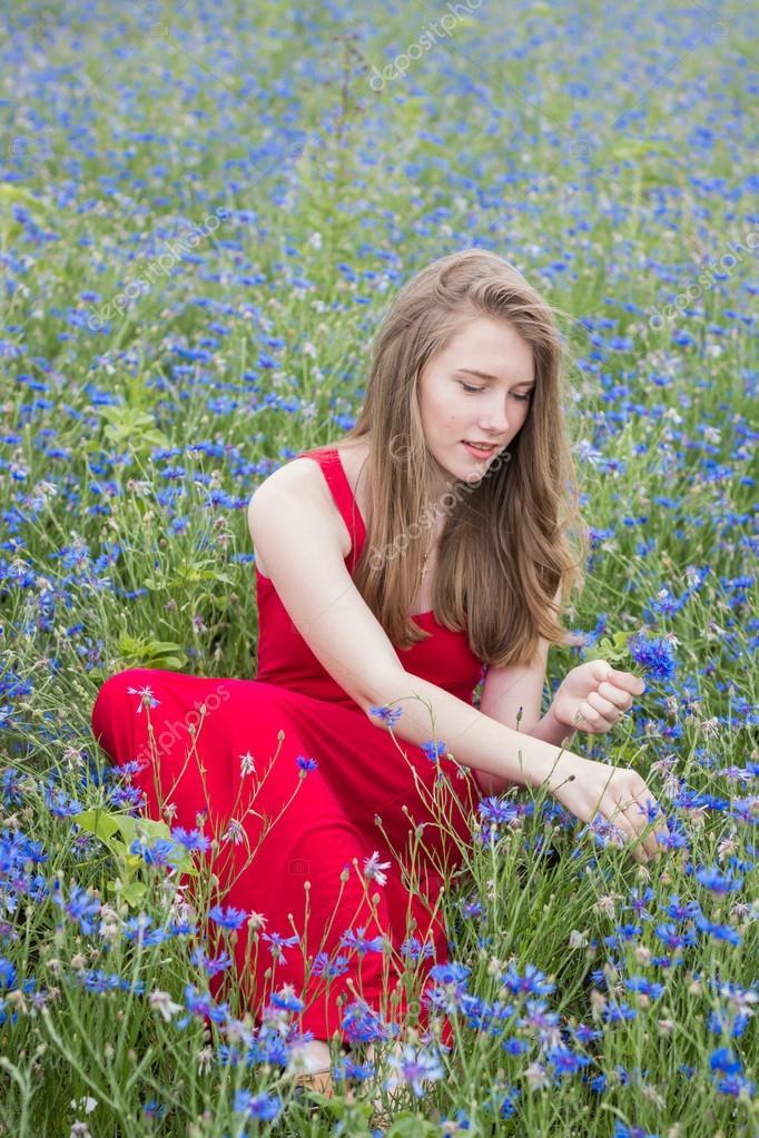 Молодая красивая улыбающаяся девушка собирает цветы на ...