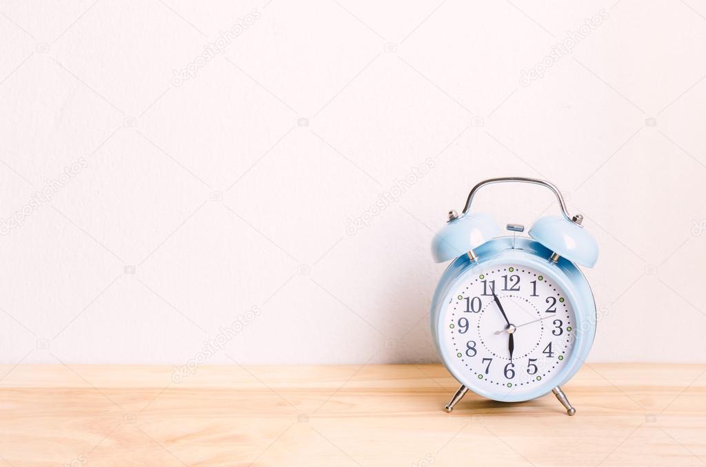Wekker Met Licht : Licht blauwe wekker op houten tafel en witte muur achtergrond