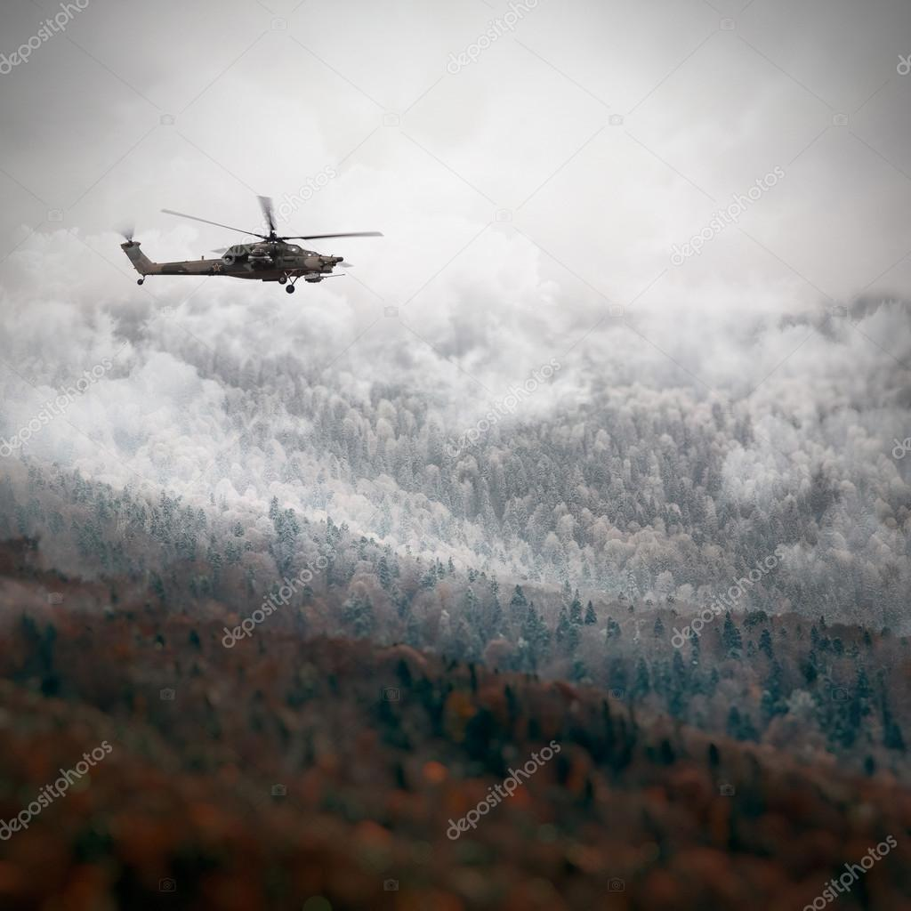 Russian Combat helicopter over the winter mountains