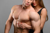 Photo Couple of athlete lovers without faces posing on grey background