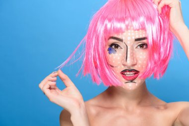 Beauty head shot. Young woman with creative pop art make up and pink wig looking at the camera on blue background