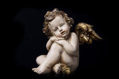 Boy angel sculpture on black background