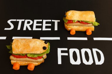 Two sandwiches shaped like  a car race in the two lanes of a street where  are placed  the letters  of white colour  that form the written english  street food stock vector