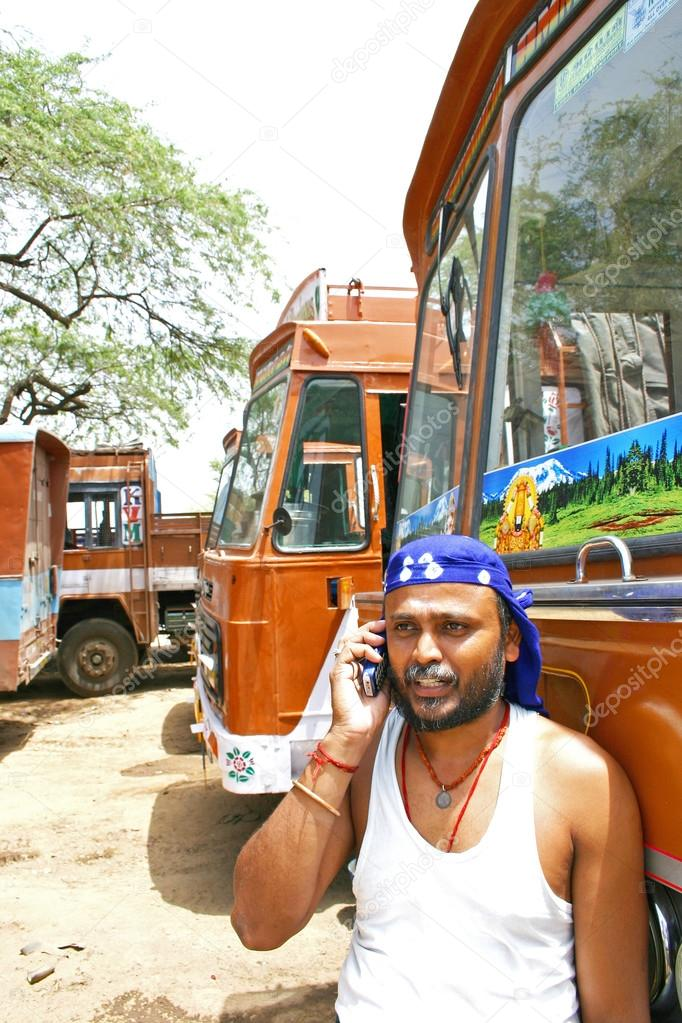 Kerala,India - July 13, 2004: Indian truck driver talking on his mobile phone with trucks parked on his back.