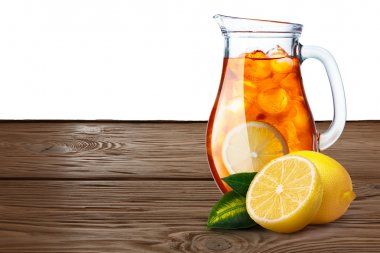 Jug or pitcher of iced tea with lemons on foreground standin on