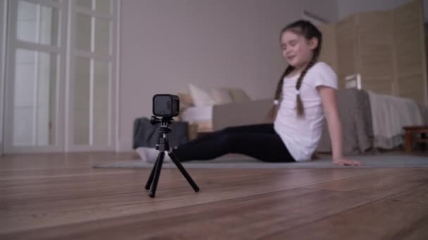 girl child broadcasts an online course and writes a vlog about gymnastics at home