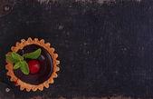 Fotografie Kuchen mit Schokolade und Kirschen auf schwarzem Hintergrund