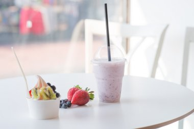 smoothie in plastic cup and frozen yougurt with fruits