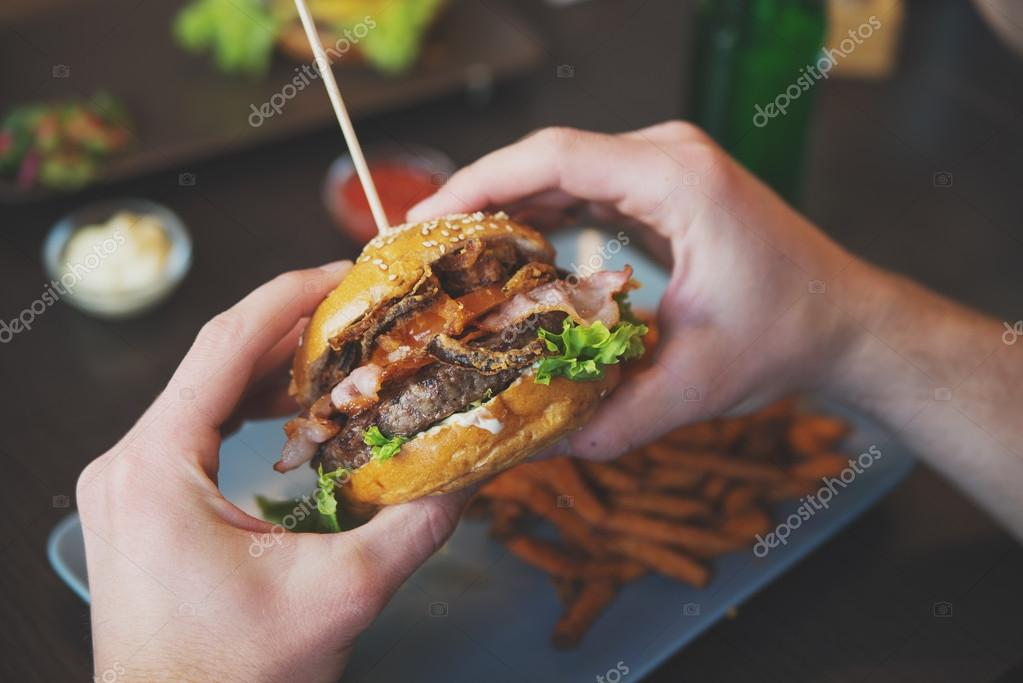 Man holds burger with hands and sweet potato fries  and dips on