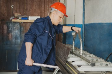 Worker working on the machine for cutting metal sheets