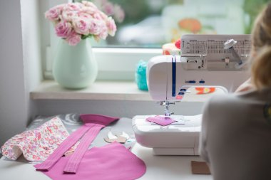 view of sewing room with sewing machine, fabric, flowers and wom