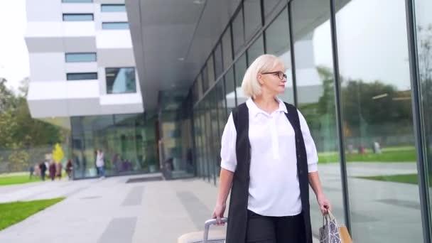 Közelkép portré magabiztos vonzó idős üzleti nő laptop és telefon a kezében a háttérben a modern épület kívül. Egy idős női professzor vagy tanár a kamerába néz és mosolyog.