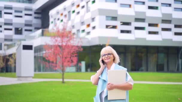 Közelkép portré magabiztos vezető üzletasszony menedzser laptop és telefon a kezében modern épület városi háttér kívül. Az öreg tanárnő vagy a főnök telefonál.
