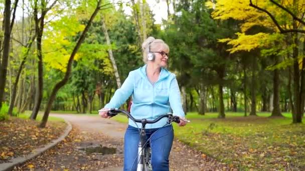 šťastná seniorka ve sluchátkách jezdí zaparkovat kolo a poslouchá hudební audio knihy. stará cyklistka s retro motorkou se věnuje aktivnímu životnímu stylu v přírodě. procházka podzimní les nebo městský park mimo