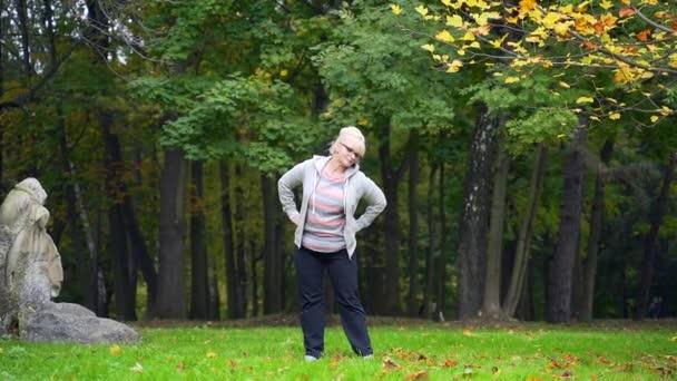 Die Seniorin macht Aerobic oder Gymnastik im Außenbereich. Eine Rentnerin um die 50 macht ein Workout. Eine alte Frau treibt Sport in der Natur. Gesunder Lebensstil