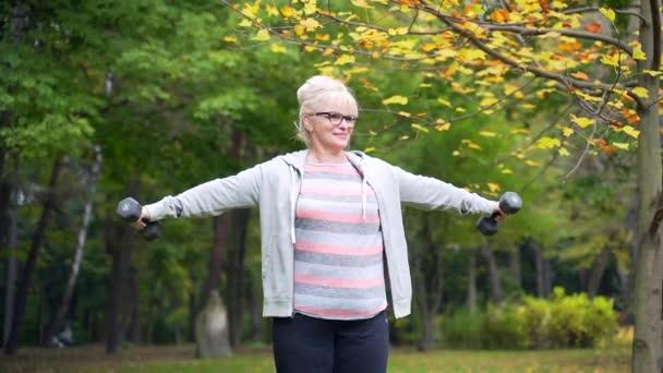 Aktive Seniorin bei körperlichen Übungen im Park oder Wald mit Hanteln in der Hand. Training Reife Frauen in der Natur in den 50er oder 60er Jahren. Sport und gesunder Lebensstil. Rentnerin im Freien ausgebildet